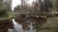 Couple hike across small bridge over river