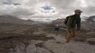 Couple hiking alpine trail, stop to enjoy view