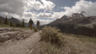 Couple hiking alpine trail under snow capped mountains