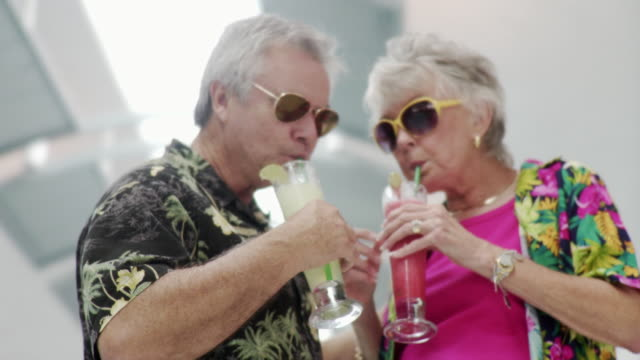 MS ZO Couple holding drinks and talking in airport concourse / Jacksonville, Florida, USA