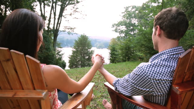Couple holding hands in lawn chairs in backyard
