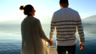 Couple holding hands on wooden pier