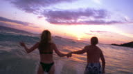 REAR VIEW couple holding hands + running + jumping into ocean at sunset / Hawaii
