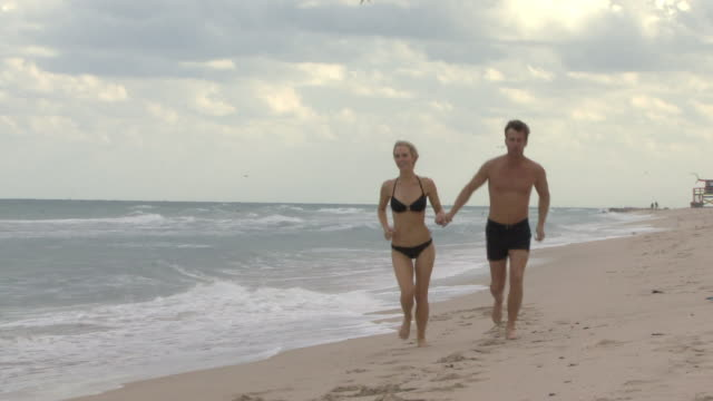 WS CU Couple holding hands running on beach / Miami, Florida, USA