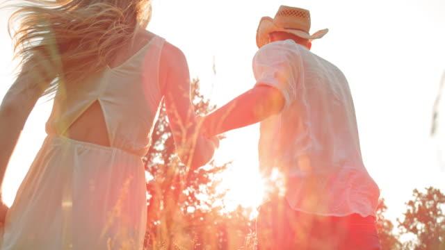 SLO MO coppia tenendo le mani correre verso il sole