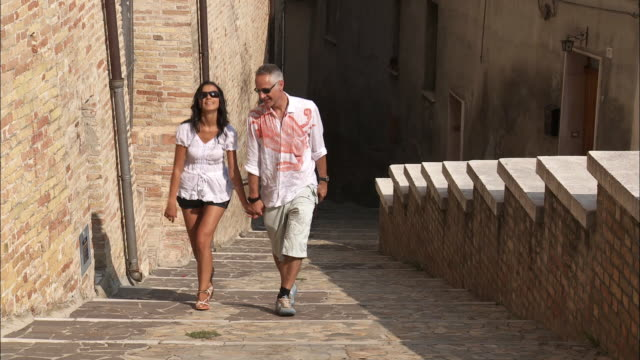 MS TU Couple holding hands walking up steps on old town street, San Viti, Abruzzi, Italy