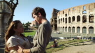Couple hug in front of the Coliseum