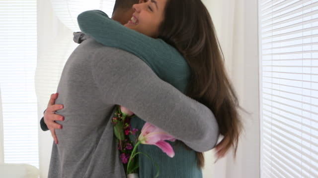 Couple hugging after boyfriend gives girlfriend bouquet