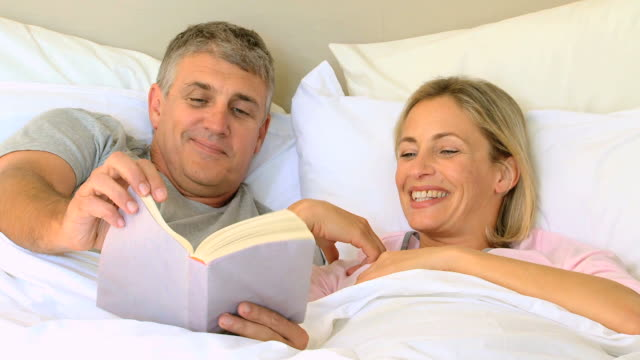 Couple in bed enjoying a book / Cape Town, Western Cape, South Africa