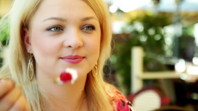 Couple in cafe, young woman flirts eating cherry with cream