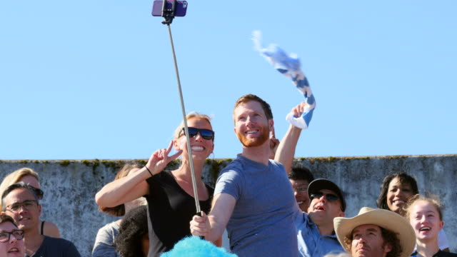 ms couple in crowd at sporting event standing up in stadium using selfie stick to take photo. Black Bedroom Furniture Sets. Home Design Ideas