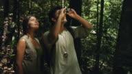 SLO MO, MS, Couple in jungle looking through binoculars, Manaus, Brazil