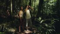 SLO MO, WS, Couple in jungle looking through binoculars, Manaus, Brazil