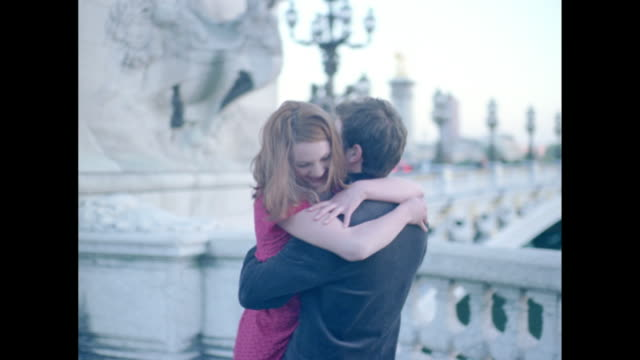 Couple in love hugging and twirling by the Seine river in Paris
