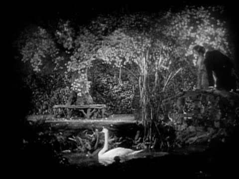 MS, CU, B&W, Couple in romantic garden at night, 1920's