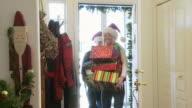 Couple in Santa Claus hats bringing presents and wrapping paper in through the front door / Bellevue, Idaho, United States