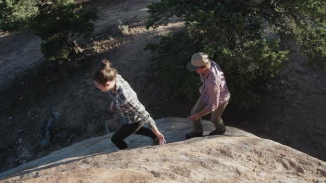 Couple in Their Twenties Walks Along Rocky Cliff