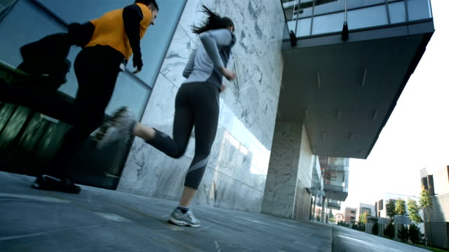 HD: Couple Jogging Along Business Buildings