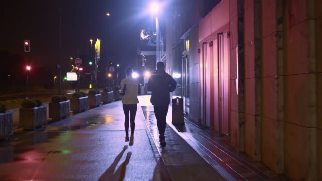 TS Couple jogging in city streets on a rainy night