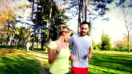 Couple jogging in park on sunny day.