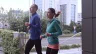 SLO MO TS paar joggen in de ochtend door stad