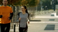 HD SLOW MOTION: Couple Jogging On Pedestrian Walkway