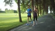 SLO MO TS Couple jogging through a park