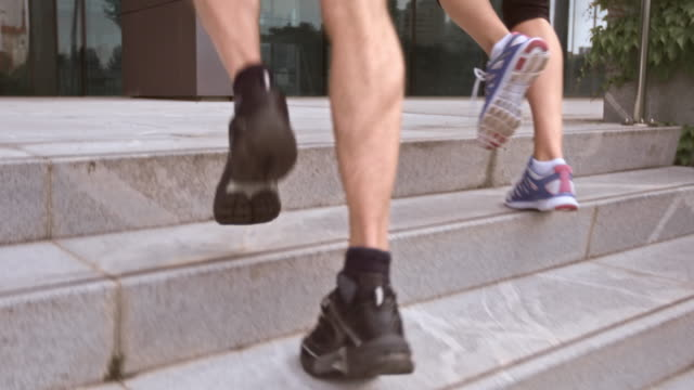 SLO MO TS Couple jogging up the stairs