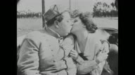 Fatty Arbuckle and Miss Cutie Cuticle (Alice Lake) kiss as they ride in a carriage