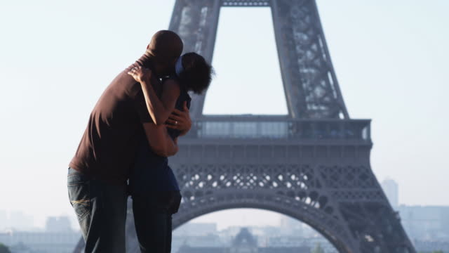 couple kissing and hugging in front of the Eiffel tower