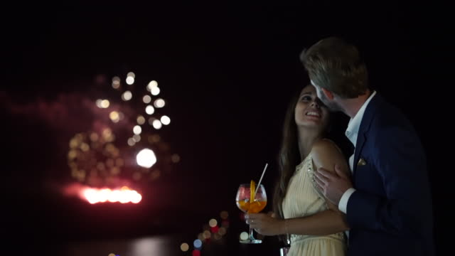 couple kissing fireworks in background
