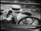 B/W 1925 couple kissing in automobile / man in straw hat / newsreel