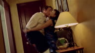 Couple kissing passionately and removing each other's clothes in apartment