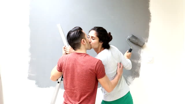 Couple kissing while painting wall with paint roller