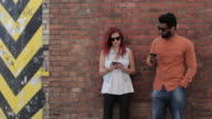Couple leaning on brick wall outside, looking at cell phones, laughing, talking