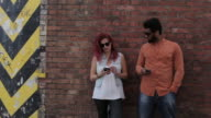 Couple leaning on brick wall outside, looking at cell phones, texting, talking on phone