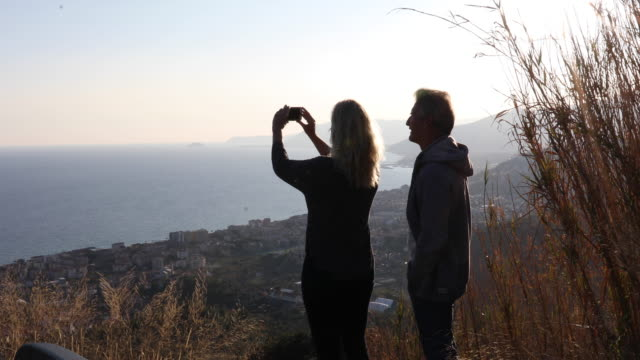 Couple leave parked car, take smart phone pic over valley, sea
