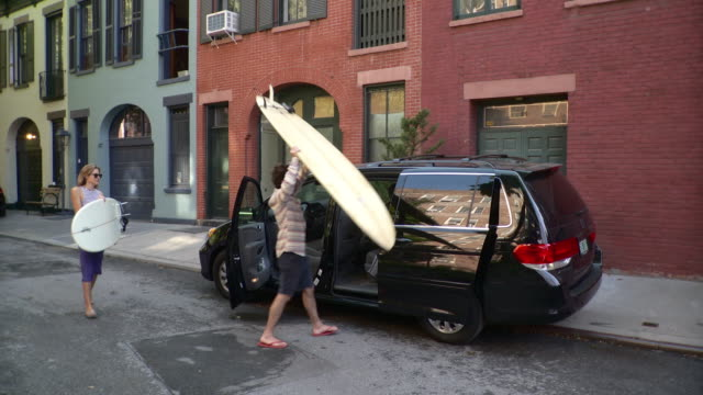 WS Couple leaving building carrying surfboards, loading them onto mini van parked on street / Brooklyn, New York City, New York State, USA
