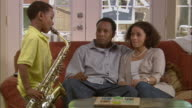 MS, PAN, couple listening to son (6-7) play saxophone in living room, Westfield, New Jersey, USA
