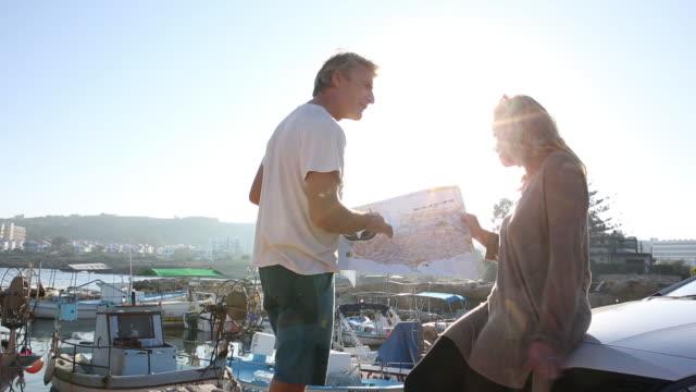 Couple look at map from parked car, at marina