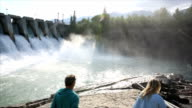 Couple look out towards hydroelectric facility at sunrise