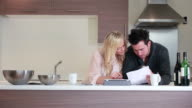 couple looking at bills in kitchen