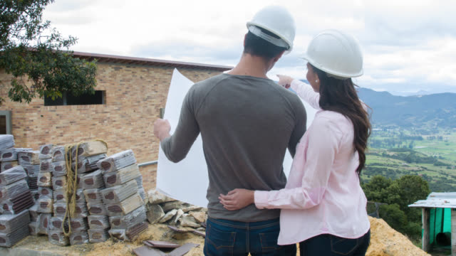Couple looking at blueprints of their house under construction