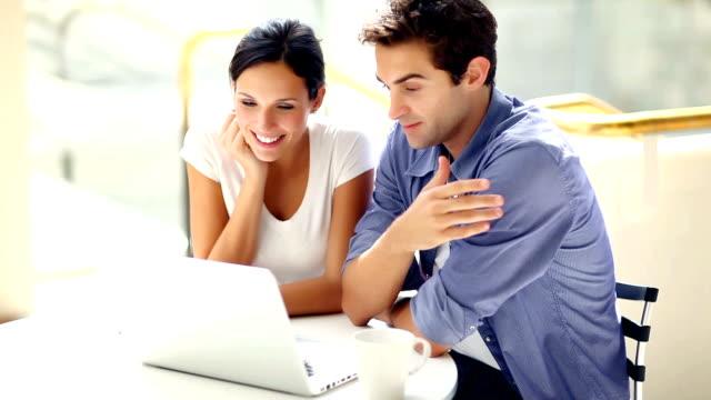 Paar Blick auf einander während Sie mit laptop im Café