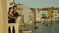 WS PAN Couple looking at Grand Canal from balcony / Venice,Veneto