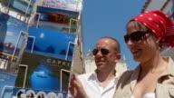 Couple looking at postcards of Capri outside Church of Santa Sofia / Capri