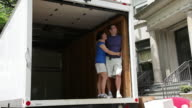 MS Couple looking  out from empty moving truck / Newark, New Jersey, United States