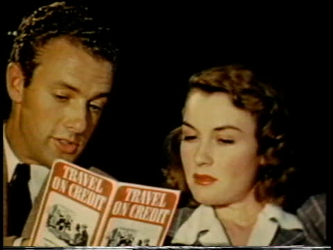 1941 CU couple looking over a 'travel on credit' brochure / United States