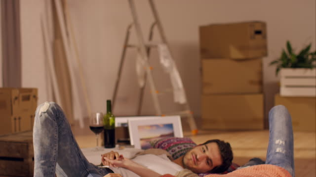 Couple lying and relaxing on carpet in new apartment