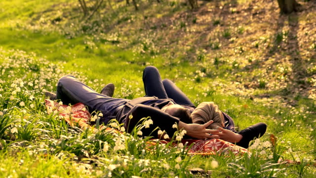 HD DOLLY: Couple Lying Between The Flowers